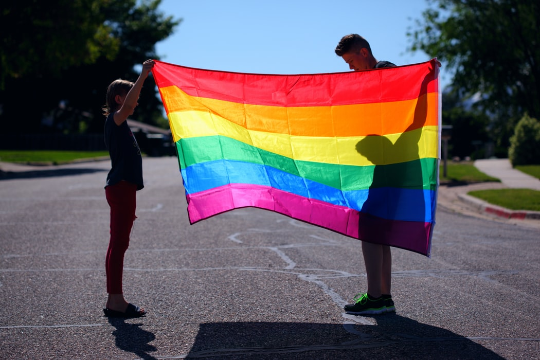 Two people holding an LGBT flag